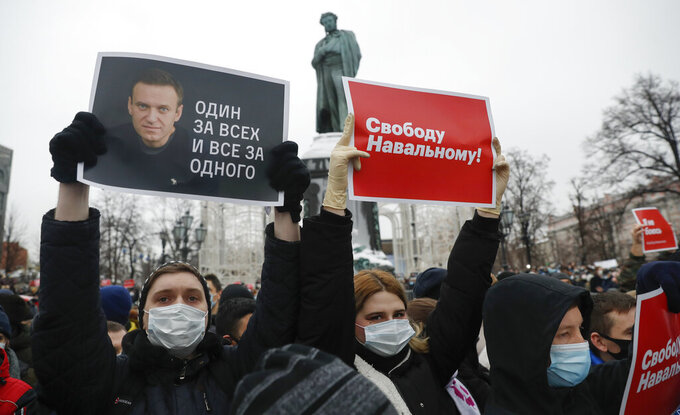 "People gather during a protest against the jailing of opposition leader Alexei Navalny in Pushkin square at the statue of Alexander Pushkin in the background in Moscow, Russia, Saturday, Jan. 23, 2021. Protesters hold posters reading ""Freedom for Navalny!"" and ""One for all and all for one"" with Navalny's portrait. Authorities in Russia have taken measures to curb protests planned for Saturday against the jailing of Navalny. (AP Photo/Pavel Golovkin)"