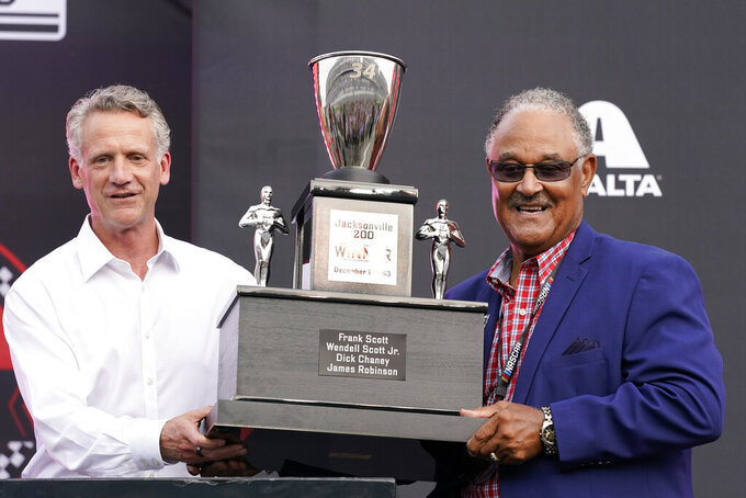 NASCAR President Steve Phelps, left, presents a trophy to Wendell Scott's son Frank Scott before the Cup Series auto race at Daytona International Speedway, Saturday, Aug. 28, 2021, in Daytona Beach, Fla. NASCAR presented Scott's family a custom trophy commemorating his historic 1963 victory. Scott was the first and remains the only Black driver to win a race at NASCAR's top level. (AP Photo/John Raoux)