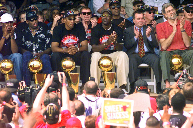 """FILE - In this June 16, 1998, file photo, NBA Champions, from left: Ron Harper, Dennis Rodman, Scottie Pippen, Michael Jordan and coach Phil Jackson are joined on stage by Chicago Mayor Richard Daley, second from right, during a city-wide rally in Chicago to celebrate the Chicago Bulls 6th NBA championship. Jordan described his final NBA championship season with the Chicago Bulls as a """"trying year."""" """"We were all trying to enjoy that year knowing it was coming to an end,"""" Jordan told Good Morning America on Thursday, April 16, 2020.  (AP Photo/Beth A. Keiser, File)"""