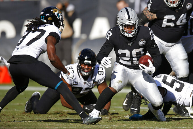 Oakland Raiders running back Josh Jacobs runs with the ball past Jacksonville Jaguars cornerback Tre Herndon (37) and Calais Campbell (93) during the first half of an NFL football game in Oakland, Calif., Sunday, Dec. 15, 2019. (AP Photo/D. Ross Cameron)