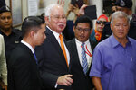 Former Malaysian Prime Minister Najib Razak, second from left, leaves Kuala Lumpur High Court in Kuala Lumpur, Monday, Nov. 11, 2019.A Malaysian judge on Monday ordered Najib to enter a defense at his first corruption trial linked to the multibillion-dollar looting at the 1MDB state investment fund that helped spur his shocking election ouster last year. (AP Photo/Vincent Thian)