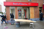 Carpenters board up a Bank of America branch, Wednesday, Oct. 28, 2020, on Court Street in the Boerum Hill neighborhood of the Brooklyn borough of New York. Demonstrators protesting the police shooting of a Black man in Philadelphia broke store windows, set fires and vandalized police cars in Brooklyn Tuesday night, police said. (AP Photo/Mary Altaffer)