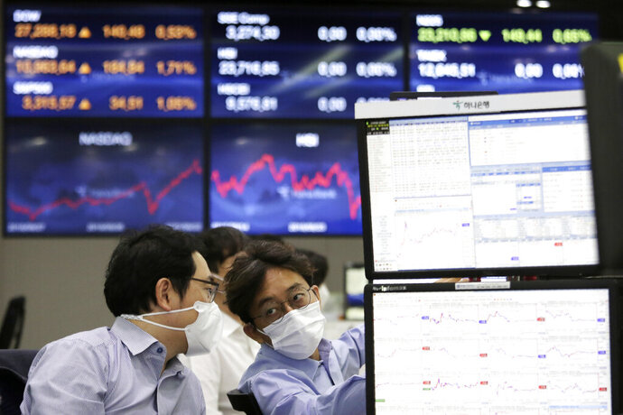 Currency traders work at the foreign exchange dealing room of the KEB Hana Bank headquarters in Seoul, South Korea, Wednesday, Sept. 23, 2020. Asian markets were mostly lower on Wednesday as investors kept a wary eye on how the coronavirus pandemic will affect the economic outlook. (AP Photo/Ahn Young-joon)