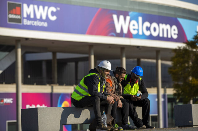 Workers at the Mobile World Congress sit outside the venue in Barcelona, Spain, Thursday, Feb. 13, 2020. Organizers of the world's biggest mobile technology fair are pulling the plug over worries about the viral outbreak from China. The annual Mobile World Congress will no longer be held as planned in Barcelona, Spain, on Feb. 24-27. (AP Photo/Emilio Morenatti)