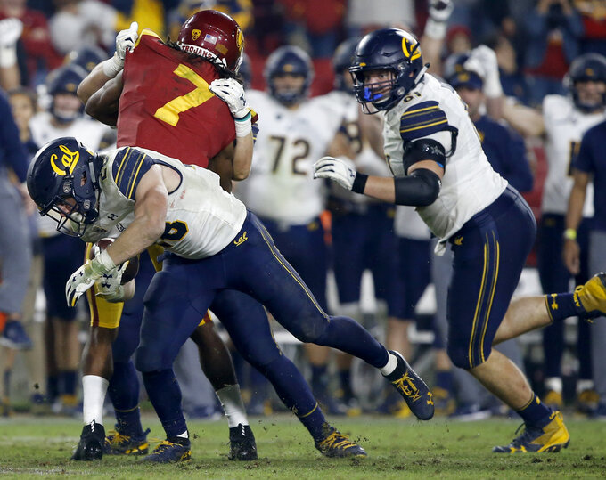 California running back Patrick Laird, left, runs for a first down on fourth-and-one, as Southern California safety Marvell Tell III (7) gets blocked during the second half of an NCAA college football game in Los Angeles, Saturday, Nov. 10, 2018. California won 15-14. (AP Photo/Alex Gallardo)