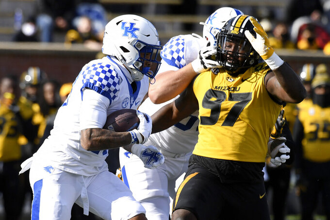 Kentucky running back Asim Rose Jr., left runs past Missouri defensive lineman Akial Byers (97) during the first half an NCAA college football game Saturday, Oct. 24, 2020, in Columbia, Mo. (AP Photo/L.G. Patterson)