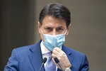 Italian Premier Giuseppe Conte adjusts his face mask as he announces new rules to curb the spread of COVID-19, in Rome, Sunday, Oct. 25, 2020. For at least the next month, people outdoors except for small children must now wear masks in all of Italy, gyms, cinemas and movie theaters will be closed, ski slopes are off-limits to all but competitive skiers and cafes and restaurants must shut down in early evenings, under a decree signed on Sunday by Italian Premier Giuseppe Conte, who ruled against another severe lockdown despite a current surge in COVID-19 infections. (Roberto Monaldo/LaPresse via AP)