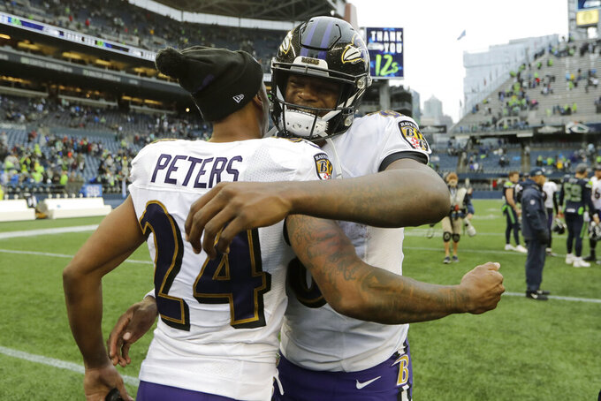 Baltimore Ravens quarterback Lamar Jackson, right, hugs cornerback Marcus Peters (24) after an NFL football game, Sunday, Oct. 20, 2019, in Seattle. (AP Photo/John Froschauer)