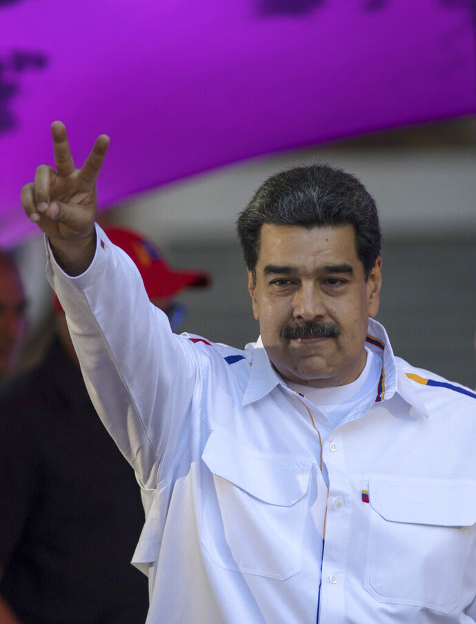 Venezuela's President Nicolas Maduro greets supporters during a pro-government demonstration in Caracas, Venezuela, Tuesday, Feb. 12, 2019. Venezuela's opposition is calling supporters into the streets across the country in a campaign to break the military's support of President Nicolas Maduro. The demonstrations come after more than a month of pressure led by opposition lawmaker Juan Guaido, while Maduro remains firmly in power and at the military's helm. (AP Photo/Rodrigo Abd)