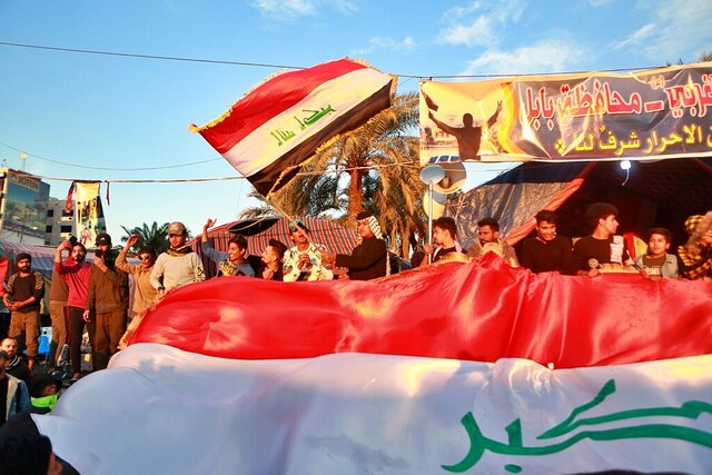 Anti-government protesters chant slogans while holding the national flags during a demonstration against the newly appointed Prime Minister Mohammed Allawi in Tahrir Square, Baghdad, Iraq, Monday, Feb. 3, 2020. (AP Photo/Khalid Mohammed)