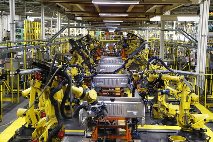 In this Sept. 27, 2018 file photo, robots weld the bed of a 2018 Ford F-150 truck on the assembly line at the Ford Rouge assembly plant in Dearborn, Mich. The U.S. auto industry's coronavirus comeback plan was pretty simple: restart factories gradually and push out trucks and other vehicles for waiting buyers in states left largely untouched by the virus outbreak. Yet the return from a two-month production shutdown hasn't gone quite according to plan.  (AP Photo/Carlos Osorio, File)