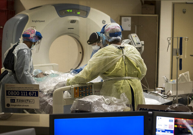 Medical workers prepare a COVID positive patient for a CT Scan at a clinic in Johannesburg Sunday, Dec. 27, 2020. South Africa's COVID-19 spike has taken the country to more than 1 million confirmed cases with hospitals reaching capacity and no sign of the new surge reaching a peak. (AP Photo/Shiraaz Mohamed.