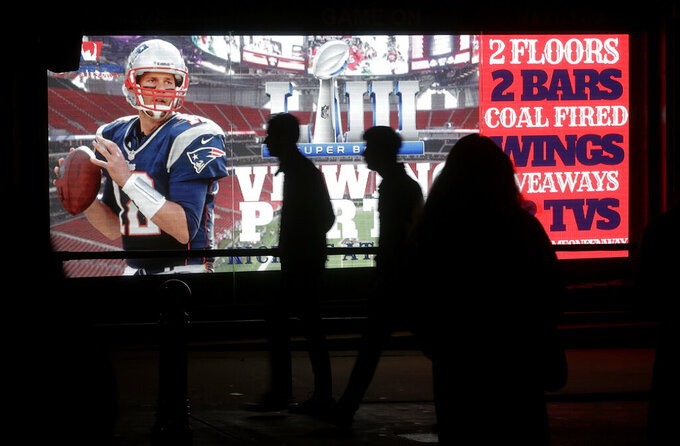 Fans walk past a bar's sign showing New England Patriots' Tom Brady before the NFL Super Bowl 53 football game in Atlanta between the Patriots and the Los Angeles Rams, Sunday, Feb. 3, 2019, in Boston. (AP Photo/Steven Senne)