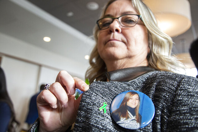 This Jan. 9, 2020 photo shows Bonnie Raffaele of Sault Ste. Marie, Mich., with a photo of her late daughter, Kelsey, 17, who died while using her cellphone while driving in 2010. Gov. Gretchen Whitmer and safety advocates want to combat distracted driving by restricting the use of cellphones, though pending legislation does not go as far as what she proposed in 2019. (Mandi Wright/Detroit Free Press via AP)