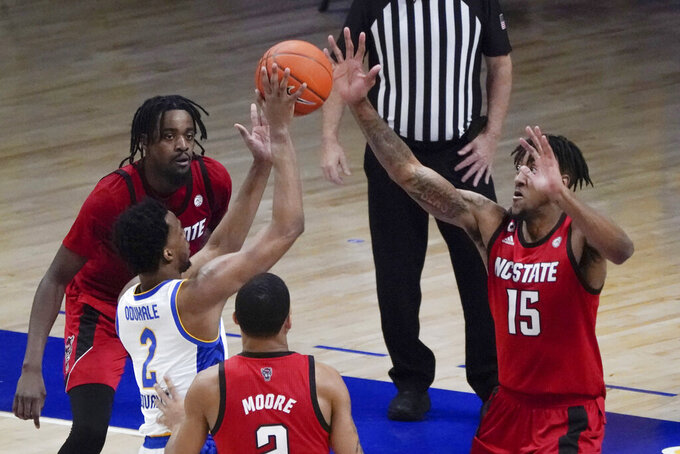 North Carolina State's Manny Bates (15) blocks a shot by Pittsburgh's Femi Odukale (2) during the second half of an NCAA college basketball game, Wednesday, Feb. 17, 2021, in Pittsburgh. North Carolina State won 74-73. (AP Photo/Keith Srakocic)