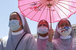 Nuns wearing protective masks take shelter from the sun as they attend the Angelus prayer celebrated by Pope Francis from his studio window overlooking St. Peter's Square at the Vatican, Sunday, July 5, 2020. (AP Photo/Riccardo De Luca)