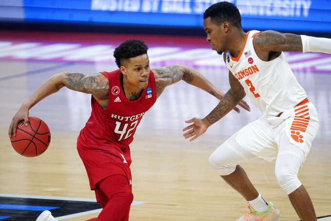 Rutgers guard Jacob Young (42) drives on Clemson guard Al-Amir Dawes (2) during the second half of a men's college basketball game in the first round of the NCAA tournament at Bankers Life Fieldhouse in Indianapolis, Friday, March 19, 2021. (AP Photo/Paul Sancya)