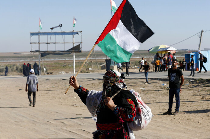 In this Sept. 25, 2019 photo, a Palestinian woman waves a national flag during a alternative protest organized by activist Ahmed Abu Artima near the separation fence between the Gaza Strip and Israel, east of Gaza City. Gaza's Hamas rulers are facing a rare and growing chorus of criticism, with little to show after 18 months of mass protests along the Israeli border organized by the Palestinian militant group. Gazans are increasingly questioning the high number of casualties and lack of success in lifting the Israeli blockade. Against this backdrop, Artima has launched his own peaceful version of the protest. (AP Photo/Adel Hana)