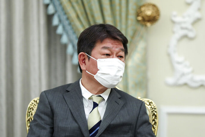 In this photo released by the official website of the office of the Iranian Presidency, Japanese Foreign Minister Toshimitsu Motegi listens to Iranian President Ebrahim Raisi during their meeting at the presidency office, in Tehran, Iran, Sunday, Aug. 22, 2021. (Iranian Presidency Office via AP)