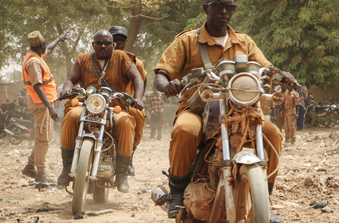 A group of local defense force fighters drive their motorbikes during an event to inaugurate a new chapter of the group in Ouagadougou, Burkina Faso, Saturday, March 14, 2020. In an effort to combat rising jihadist violence, Burkina Faso's military has recruited volunteers to help it fight militants. (AP Photo/Sam Mednick)