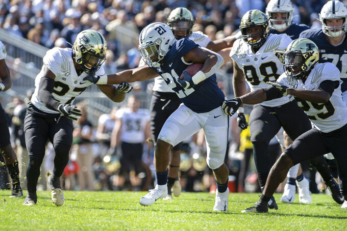 Penn State running back Noah Cain (21) stiff arms Purdue safety Navon Mosley (27) in the fourth quarter of an NCAA college football game in State College, Pa., on Saturday, Oct. 5, 2019. Penn State defeated Purdue 35-7. (AP Photo/Barry Reeger)