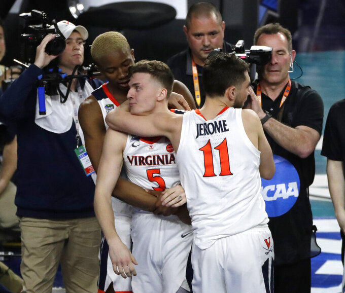 Virginia guard Kyle Guy (5) celebrates with teammates Mamadi Diakite, left, and Ty Jerome, right, after a semifinal round game against Auburn in the Final Four NCAA college basketball tournament, Saturday, April 6, 2019, in Minneapolis. (AP Photo/Matt York)