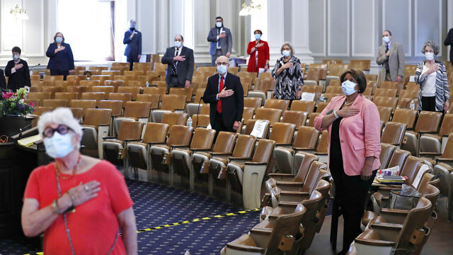 Members of the N.H. Senate stand for the Pledge of Allegience as they gather for a session on Tuesday, June 16, 2020 at the State House in Concord, New Hampshire. The 24 N.H. Senators met in the N.H. House Chamber while adhering to social distancing rules due to the COVID-19 virus outbreak. (AP Photo/Charles Krupa)
