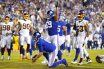 New York Giants quarterback Daniel Jones (8) gets up after after scoring a touchdown against the Washington Football Team during the first half of an NFL football game, Thursday, Sept. 16, 2021, in Landover, Md. Throwing his arms up is teammate New York Giants center Billy Price (69). (AP Photo/Patrick Semansky)