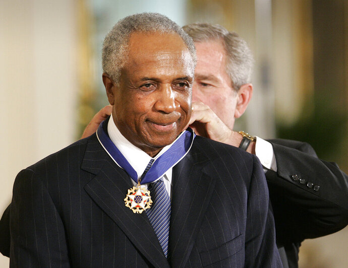 FILE - In this Nov. 9, 2005, file photo, President Bush awards baseball legend Frank Robinson the Presidential Medal of Freedom Award in the East Room of the White House in Washington. Hall of Famer Frank Robinson, the first black manager in Major League Baseball and the only player to win the MVP award in both leagues, died Feb. 7, 2019. He was 83.  (AP Photo/Lawrence Jackson, File)