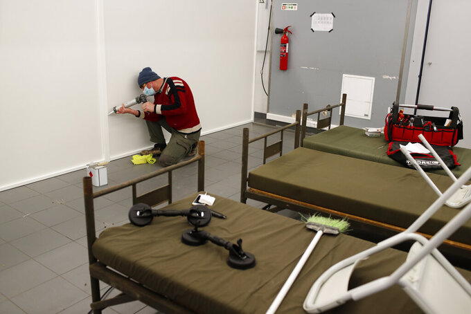 A worker finishes a panel just assembled in the Military Hospital canteen being transformed into a 50-bed infirmary, in Lisbon, Wednesday, Jan. 27, 2021. At the hospital, hundreds of troops have spent frantic weeks this month rushing to turn every available space into makeshift COVID-19 wards, as Portugal scrambles to cope with a sudden deluge of cases engulfing the public health system. (AP Photo/Armando Franca)