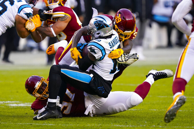 Carolina Panthers wide receiver Curtis Samuel (10) is stopped by Washington Football Team defensive tackle Tim Settle (97) and Washington Football Team defensive back Jeremy Reaves (39) during the first half of an NFL football game, Sunday, Dec. 27, 2020, in Landover, Md. (AP Photo/Susan Walsh)