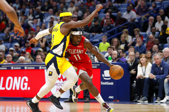 New Orleans Pelicans guard Jrue Holiday (11) drives to the basket against his brother, Indiana Pacers guard Aaron Holiday (3), during the second half of an NBA basketball game in New Orleans, Saturday, Dec. 28, 2019. The Pelicans won 120-98. (AP Photo/Gerald Herbert)