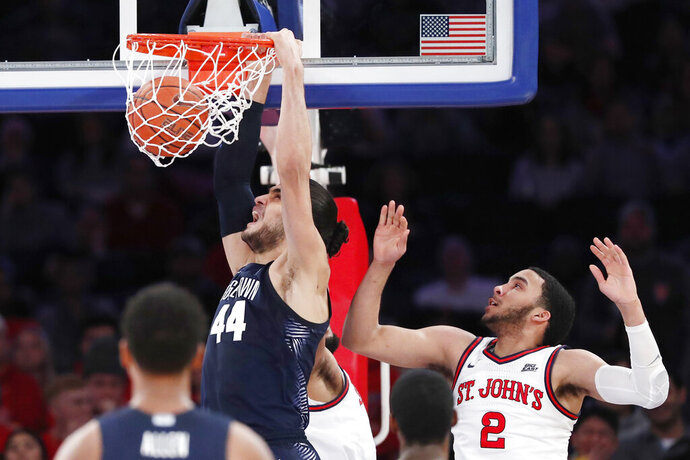Georgetown center Omer Yurtseven (44) dunks as St. John's guard Julian Champagnie (2) watches during the second half of an NCAA college basketball game, Sunday, Feb. 2, 2020, in New York. (AP Photo/Kathy Willens)