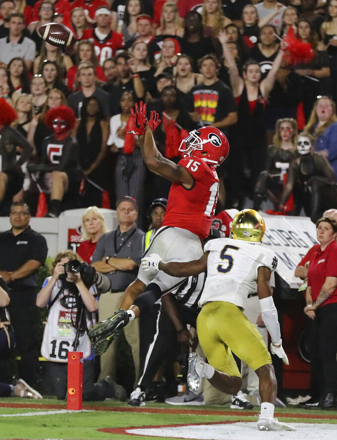 Georgia wide receiver Lawrence Cager catches a touchdown pass over Notre Dame cornerback Troy Pride Jr. during the fourth quarter of an NCAA college football game Saturday, Sept. 21, 2019, in Athens, Ga. (Curtis Compton/Atlanta Journal Constitution via AP)