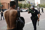 FILE - In this June 2, 2020, file photo, a police officer aims his less-lethal weapon at a demonstrator during a protest in Los Angeles. Two reviews of the violence that surrounded last summer's police brutality protests in Los Angeles say the LAPD wasn't prepared to react when peaceful demonstrations were marred by clashes, vandalism and looting. The Los Angeles Times says the reports, released Friday, April 9, 2021 found that poor planning, inconsistent leadership and inadequate training contributed to disorder in the streets that caused an estimated $167 million in losses to private property and businesses owners.  (AP Photo/Jae C. Hong, File)
