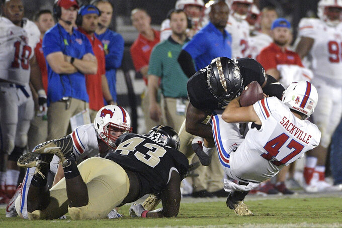 SMU punter Jamie Sackville (47) is stopped short of a first down by Central Florida defensive lineman Aaron Cochran (43) and defensive lineman Titus Davis on a fake punt play during the second half of an NCAA college football game Saturday, Oct. 6, 2018, in Orlando, Fla. UCF won 48-20. (AP Photo/Phelan M. Ebenhack)