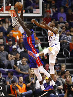 Phoenix Suns forward Josh Jackson (20) defends as Detroit Pistons forward Thon Maker (7) shoots during the second half of an NBA basketball game Thursday, March 21, 2019, in Phoenix. Jackson was injured on the play and left the game. (AP Photo/Matt York)