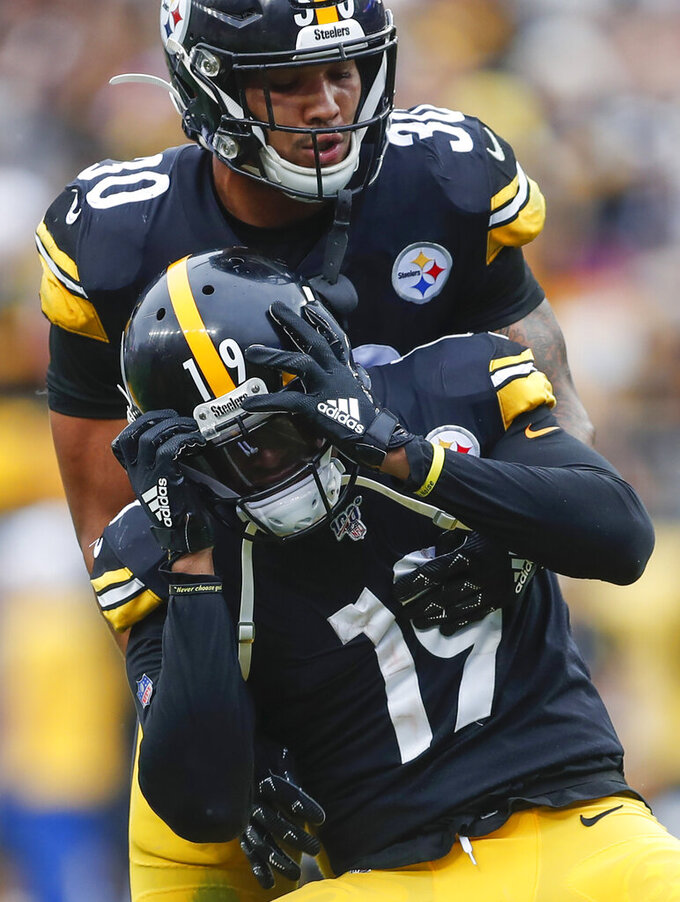 Pittsburgh Steelers running back James Conner (30) holds onto wide receiver JuJu Smith-Schuster (19) who reacts after quarterback Mason Rudolph (2) was injured in the second half of an NFL football game against the Baltimore Ravens, Sunday, Oct. 6, 2019, in Pittsburgh. (AP Photo/Don Wright)