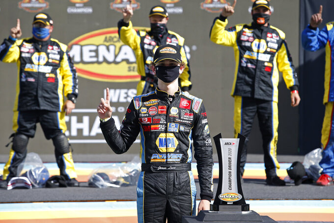 Jesse Love, center, stands with the season championship trophy following an ARCA Series auto race at Phoenix Raceway, Saturday, Nov. 7, 2020, in Avondale, Ariz. (AP Photo/Ralph Freso)