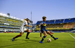 Boca Juniors' Yamila Rodriguez, right, shields the ball from Lanus' Mayra Gauna during the Superliga women's soccer tournament in Buenos Aires, Argentina, Saturday, March 9, 2019. The women competed in one of Argentina's most famous stadiums on Saturday, a milestone for the female players who are fighting for the same rights as male soccer players in the country's most popular sport. (AP Photo/Natacha Pisarenko)