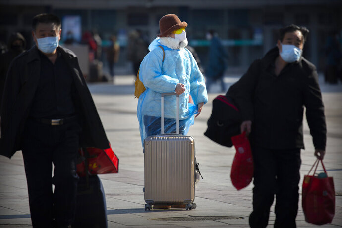 A traveler wearing face a mask, goggles, and a plastic poncho stands outside the Beijing Railway Station in Beijing, Saturday, Feb. 15, 2020. People returning to Beijing will now have to isolate themselves either at home or in a concentrated area for medical observation, said a notice from the Chinese capital's prevention and control work group published by state media late Friday. (AP Photo/Mark Schiefelbein)