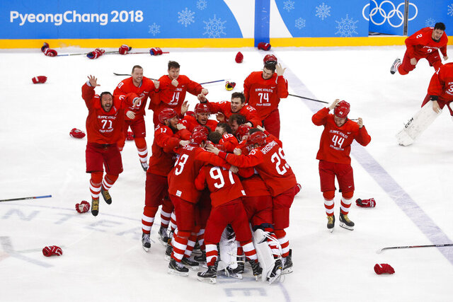 FILE - In this file photo dated Sunday, Feb. 25, 2018, Olympic athletes from Russia celebrate after winning the men's gold medal hockey game against Germany, 4-3, in overtime at the 2018 Winter Olympics, in Gangneung, South Korea.  Sanctions handed down by the World Anti-Doping Agency on Monday Dec. 9, 2019, mean there won't be a Russian flag or anthem, but athletes are still aiming for the Tokyo Olympics, and the Russian hockey players belted out the Russian national anthem, even without any music. (AP Photo/Jae C. Hong, FILE)