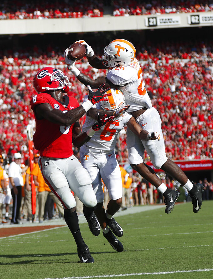FILE - In this Sept. 29, 2018, file photo, Tennessee's Trevon Flowers (25) intercepts a pass as he and Alontae Taylor (6) defend against Georgia wide receiver Riley Ridley (8) during an NCAA college football game in Athens, Ga. Flowers has a broken collarbone that will sideline him for the next few weeks, hindering the depth of the Volunteers' young secondary as they deal with the toughest portion of their schedule. (AP Photo/John Bazemore, File)