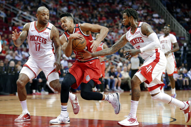 Portland Trail Blazers guard CJ McCollum, middle, drives to the basket between Houston Rockets forward PJ Tucker (17) and guard Ben McLemore, right, during the first half of an NBA basketball game Wednesday, Jan. 15, 2020, in Houston. (AP Photo/Michael Wyke)