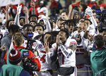 Liberty wide receiver CJ Daniels (4) and quarterback Malik Willis (7) celebrate with teammates after the team's overtime win over Coastal Carolina in the Cure Bowl NCAA college football game Saturday, Dec. 26, 2020, in Orlando, Fla. (AP Photo/Matt Stamey)