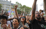 Protestors raise their fists during a demonstration in Paris, France, Saturday, July 31, 2021. Demonstrators gathered in several cities in France on Saturday to protest against the COVID-19 pass, which grants vaccinated individuals greater ease of access to venues. (AP Photo/Adrienne Surprenant)
