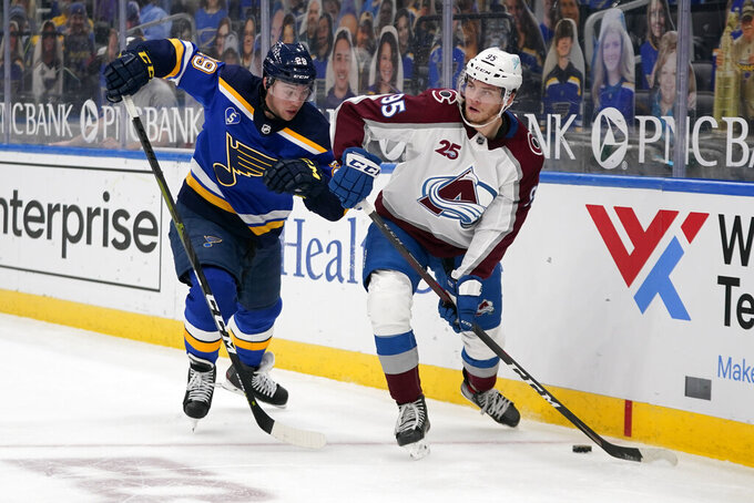 Colorado Avalanche's Andre Burakovsky (95) looks to pass as St. Louis Blues' Vince Dunn (29) defends during the third period of an NHL hockey game Thursday, April 22, 2021, in St. Louis. (AP Photo/Jeff Roberson)