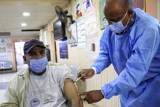 A health worker receives a dose of the Sinopharm coronavirus vaccine at a clinic in Basra, Iraq, Wednesday, March 3, 2021. (AP Photo/Nabil al-Jurani)