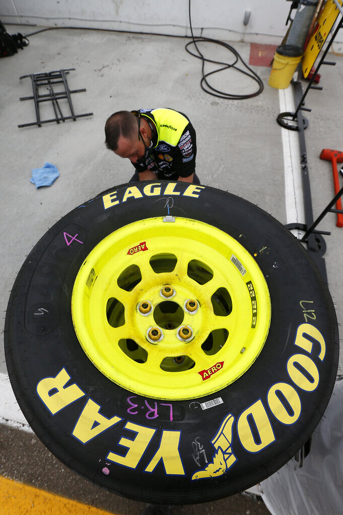 A pit crew member for driver Ryan Blaney preps tires prior to a NASCAR Cup Series auto race at Phoenix Raceway, Sunday, Nov. 8, 2020, in Avondale, Ariz. (AP Photo/Ralph Freso)