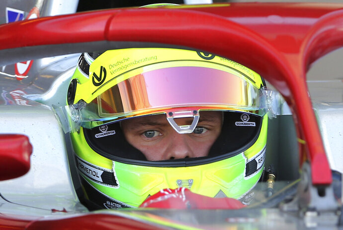 FILE - In this Friday, Nov. 30, 2018 filer, Mick Schumacher prepares for the test drive in his new formula 2 Prema racing car at the Yas Marina Circuit in Abu Dhabi, United Arab Emirates. Mick Schumacher will move closer toward emulating his father when he drives a Ferrari Formula One car in an official test next week. Ferrari says the 20-year-old Mick Schumacher will test April 2 in Bahrain. The German, who is racing in Formula Two this year with the Prema team and is a Ferrari Driver Academy member, will drive on both days of the testing session. On April 3, he will be at the wheel of an Alfa Romeo on the Sakhir circuit. Schumacher's father Michael won seven F1 titles, five of those with Ferrari from 2000-04. (AP Photo/Kamran Jebreili, File)